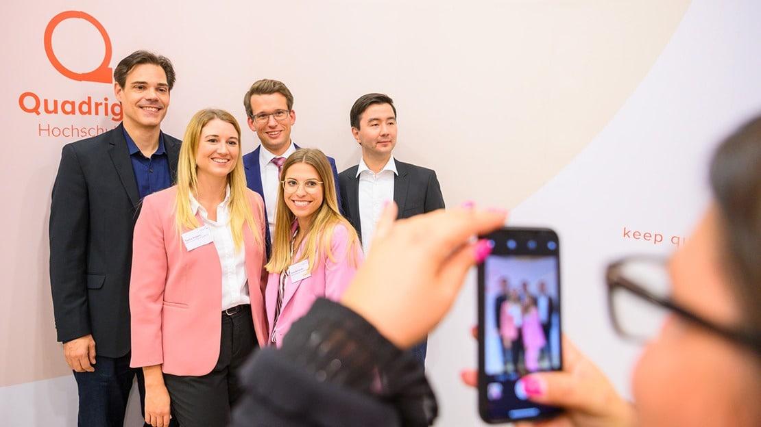Die Fotowand war ein beliebter Treffpunkt auf dem Graduation Day - hier mit Studierenden des MBA Communication.