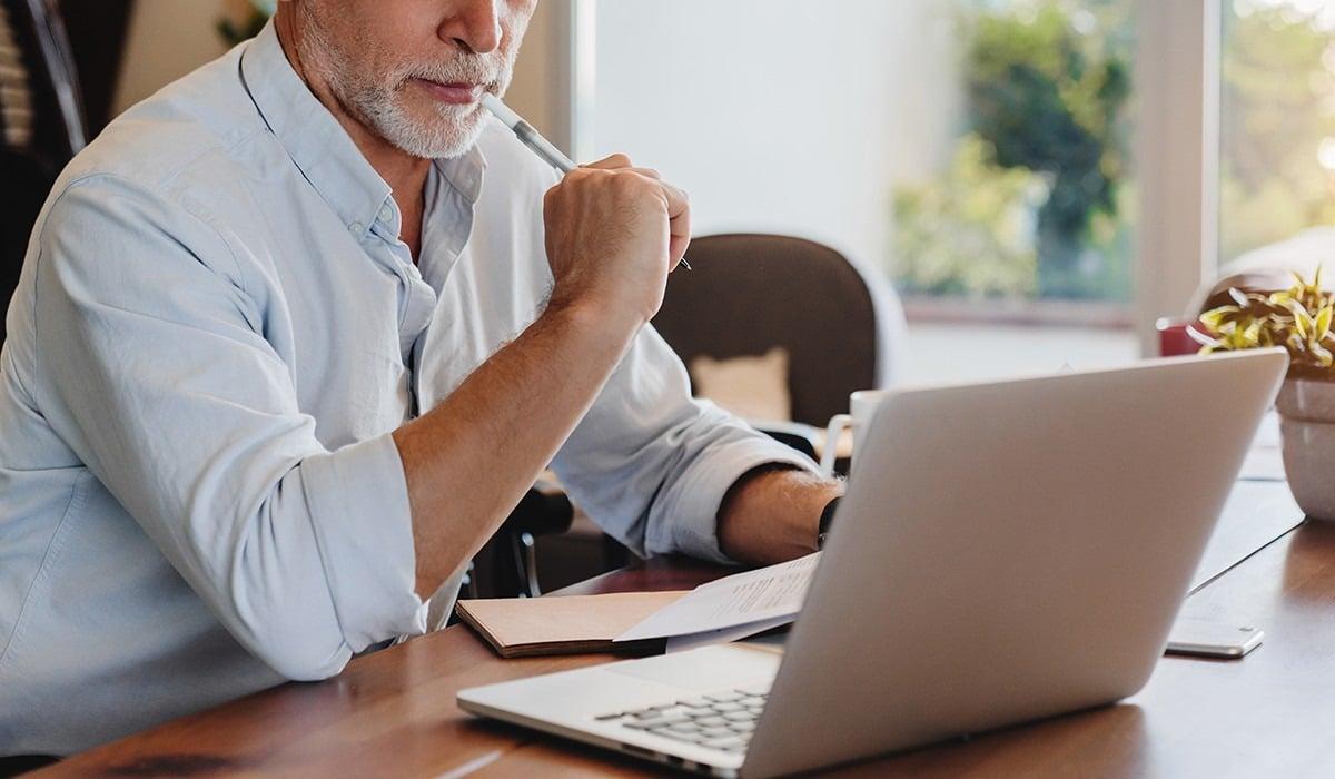 Cropped shot of senior man using laptop checking documents indoor